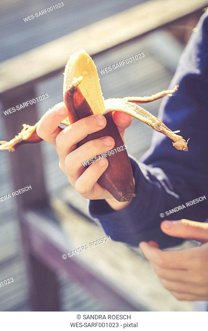 Girl's hand holding peeled red banana