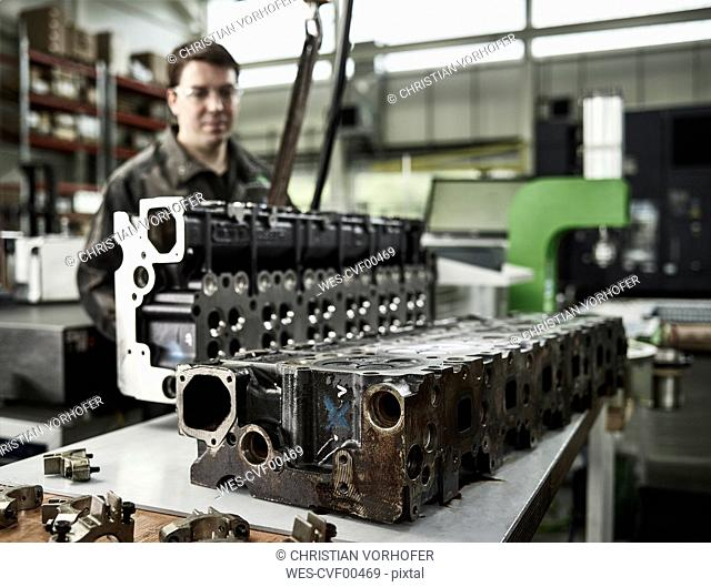 Worker in metalworking factory lifting cylinder head with crane