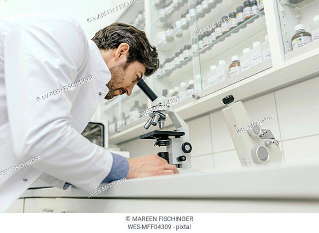 Man using microscope in laboratory