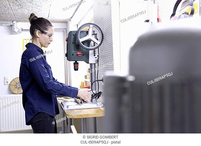 Young female carpenter drilling timber in workshop