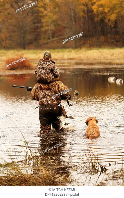 Father Carries Son Through Water With Dog While Duck Hunting