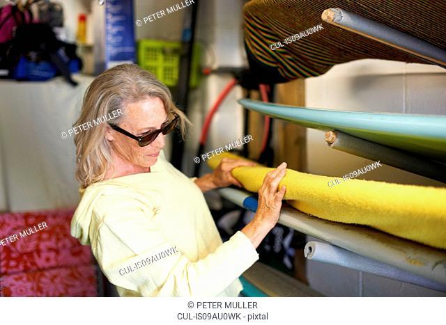 Senior woman taking surfboard from shelf