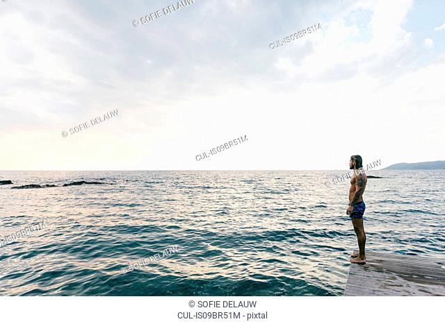 Man standing on edge of sea