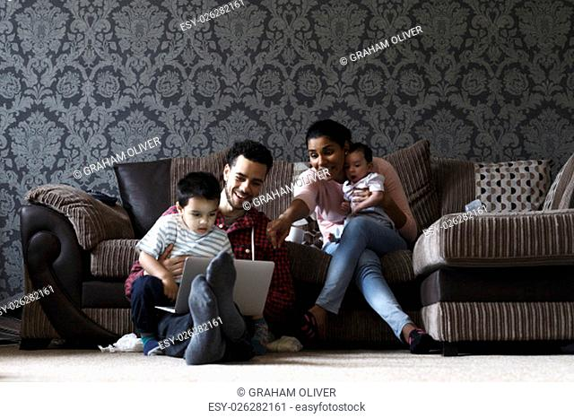 Family of four enjoying time together at home. The father is sitting on the floor with a laptop and the eldest son. The mother is sitting on the sofa with the...