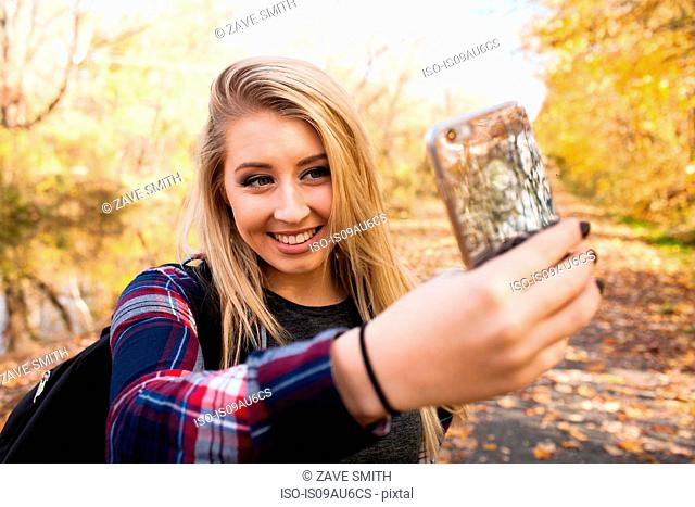 Young blond woman taking smartphone selfie in autumn forest