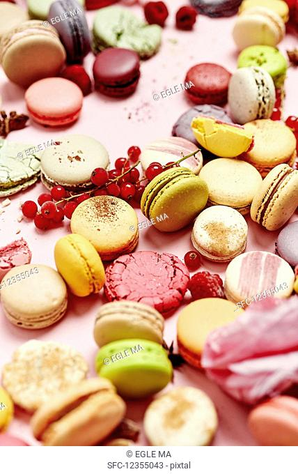 Still life of different varieties of French macarons on a pink background