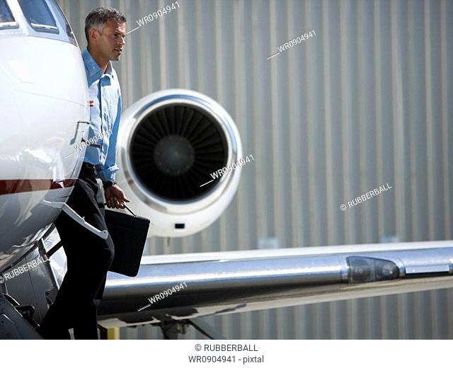 Profile of a businessman exiting an airplane