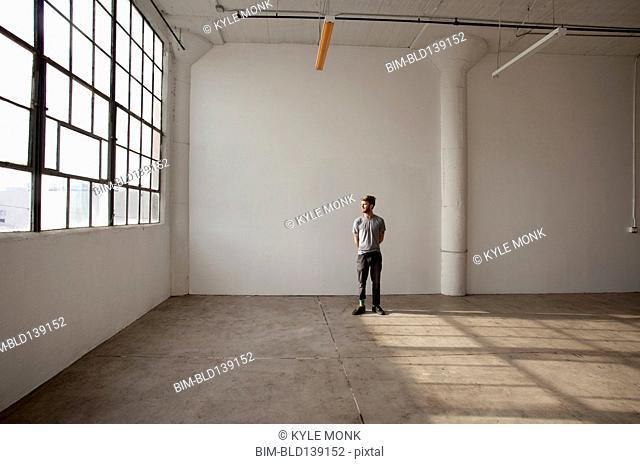 Caucasian man standing in empty loft