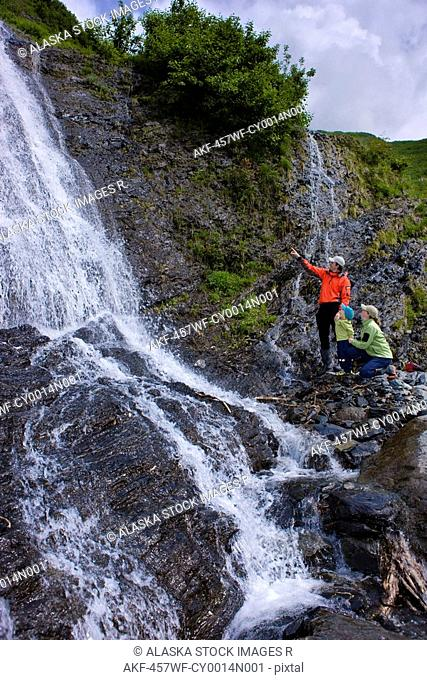 Family stands near a waterfall while hiking, Shoup Bay State Marine Park, Prince William Sound, Southcentral Alaska, Summer