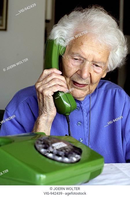 Senior woman telephoning at home. - BONN, GERMANY, 25/07/2008