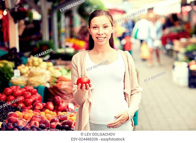sale, shopping, food, pregnancy and people concept - happy pregnant woman holding tomato at street market