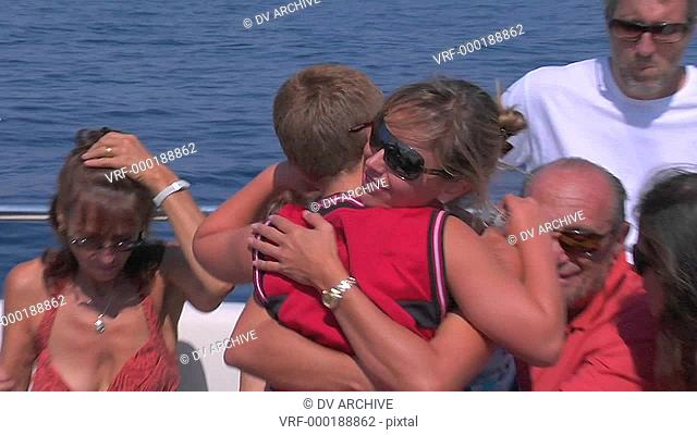 A mother hugs her son on a sailing trip