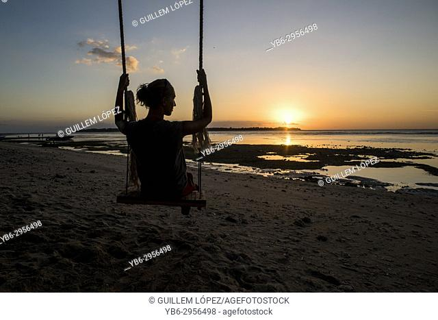 A silhouette of a young woman on a swing in a beach of Gili Air, Gili Islands, Indonesia