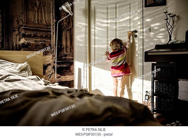 Back view of little girl opening bedroom door at home
