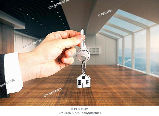 Closeup of businessman hand holding key with house keychain in modern interior. Real estate concept