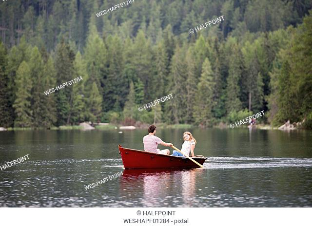 Young couple in rowing boat on the lake