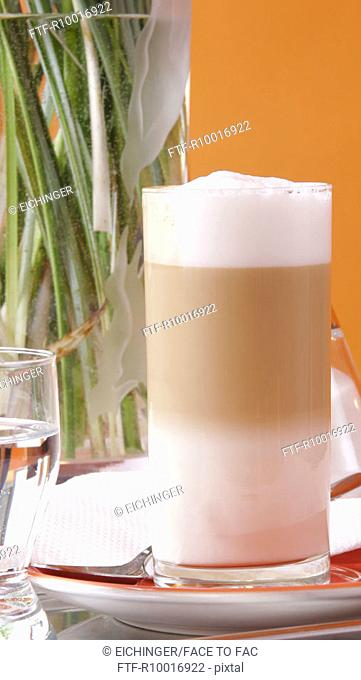 Front view of latte placed beside a glass of water