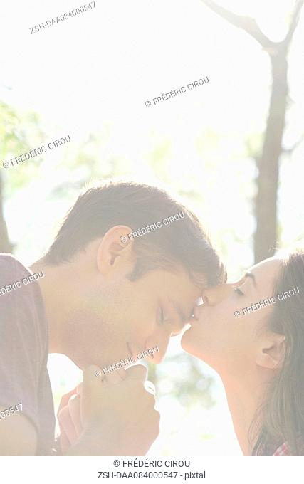 Couple together outdoors, woman kissing man's forehead