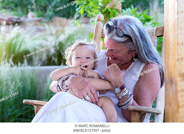 Caucasian older woman holding grandson in rocking chair