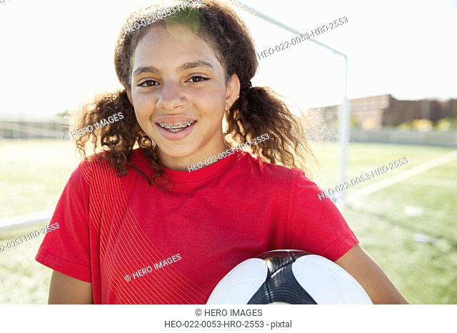 Teenage girl with soccer ball on field