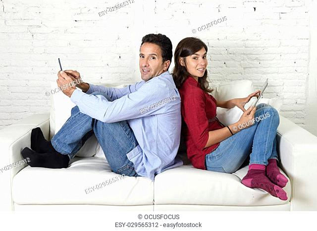 young attractive couple sitting on home couch together back to back ignoring each other using mobile phone and digital tablet in social network internet...