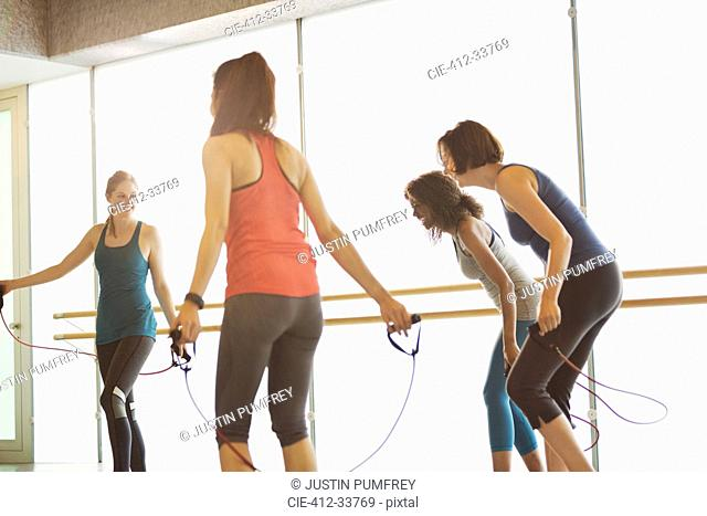 Laughing women using jump ropes in exercise class gym studio