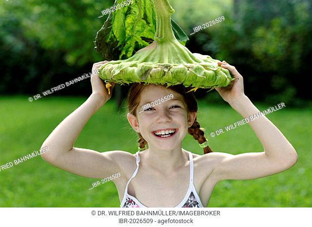 Girl with a big sunflower as a hat