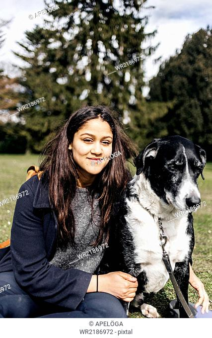 Portrait of smiling woman sitting with mixed-breed dog at park