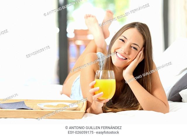 Happy girl having breakfast with orange juice on the bed at home and looking at camera