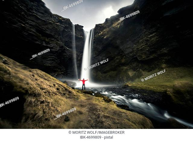 Man in red jacket in front of Kvernufoss waterfall in a gorge, dramatic atmosphere, time exposure, near Skógafoss, Southurland, Iceland