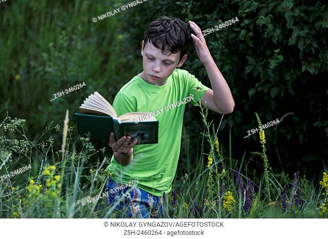 Russia. Belgorod region. Solomino village. The boy in the meadow with a book
