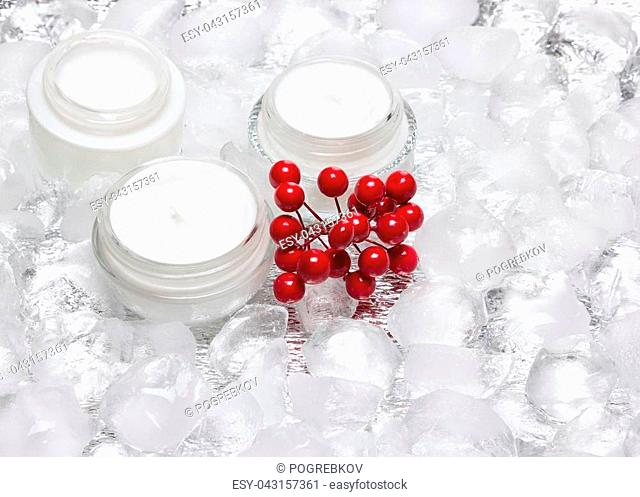 Glass jars of cream with bunch of red berries surrounded by ice cubes. Cooling effect moisturizing skin care products