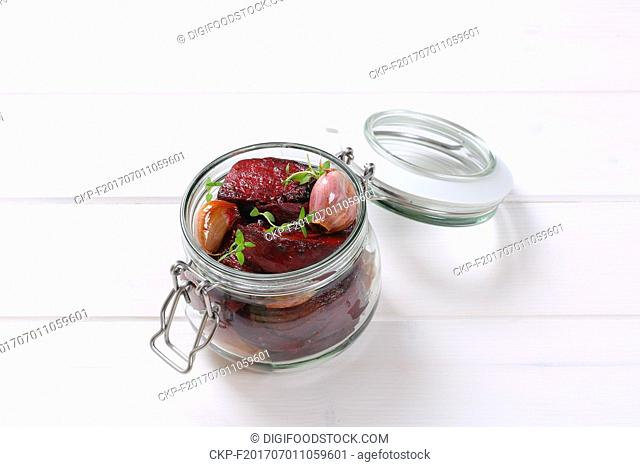 jar of baked beetroot with garlic and thyme on white wooden background