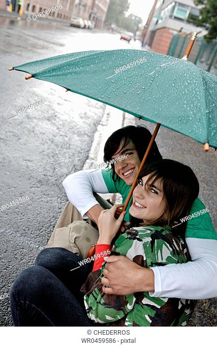 Portrait of a young man embracing a young woman under an umbrella and smiling