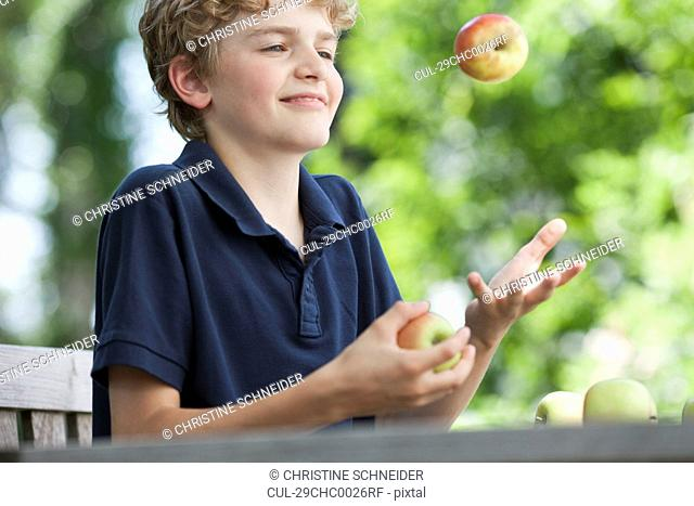 Boy juggling apples