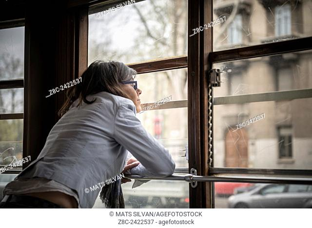 Woman traveling and looking out on a Tram window in Milan, Italy