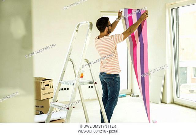 Young man renovating holding wallpaper