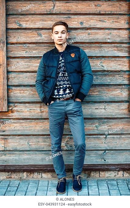 Stylish young man stands against a background of a wooden house