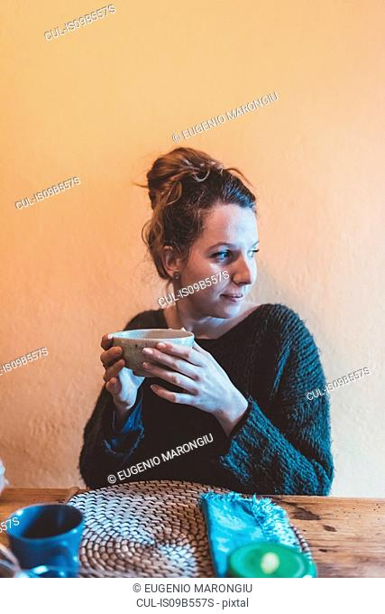 Young woman holding bowl at kitchen table