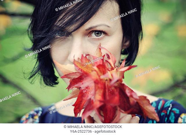 Woman holding leaves close to her face