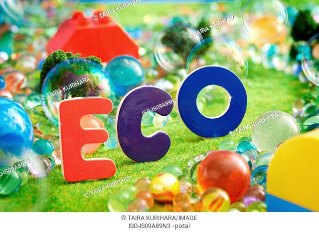 The word Eco on pretend grass with marbles