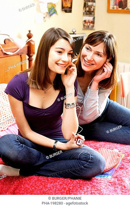 Mother and daughter listening to music with MP3 player