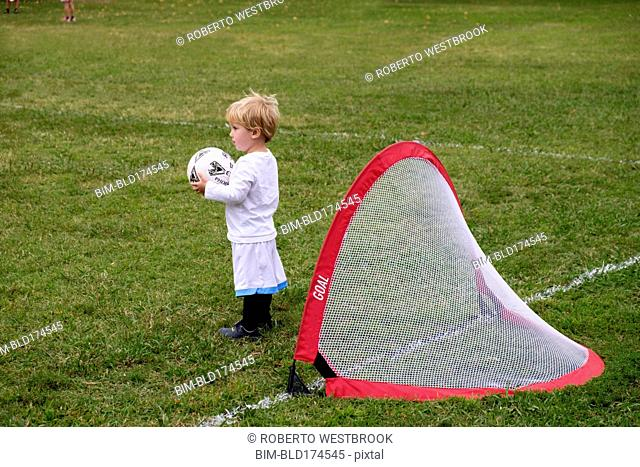Caucasian boy playing soccer in field