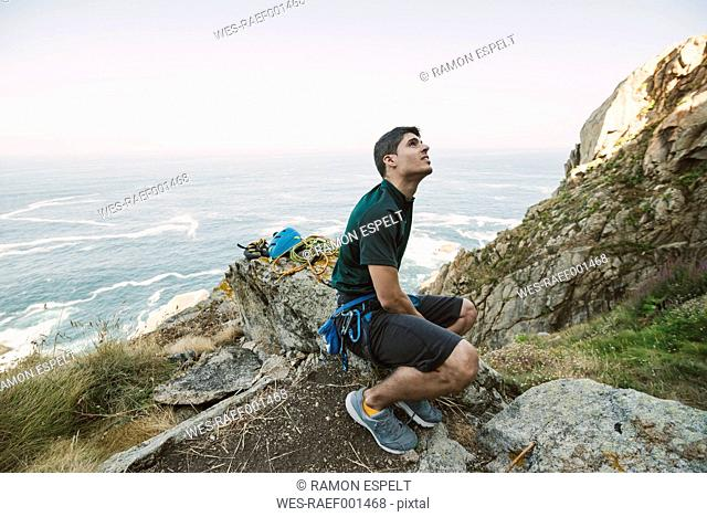 Climber sitting on a rock at the coast looking up
