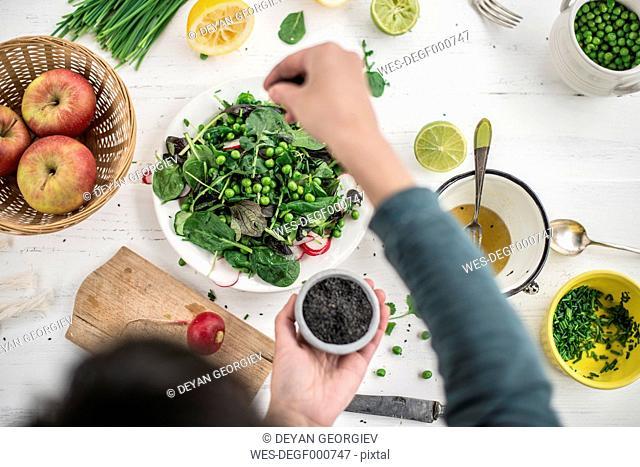 Hand preparing salad seasoning with black sesame