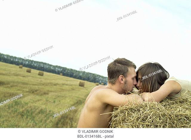 young couple having a tender moment in field of straw bales