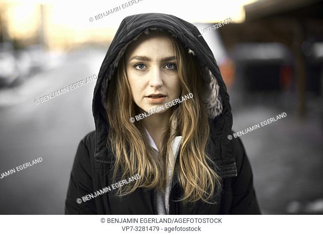 young woman outdoors, wearing hooded anorak, winter clothing, in Cottbus, Brandenburg, Germany