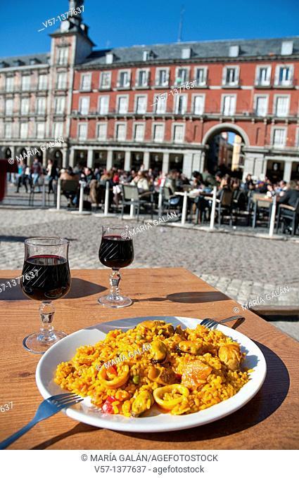 Paella Valenciana serving with red wine, Plaza Mayor. Madrid, Spain