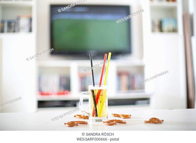 Beer mug with three drinking straws in German national colours and pretzels in front of television with empty soccer field