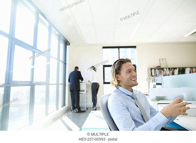 Smiling businessman at desk in office